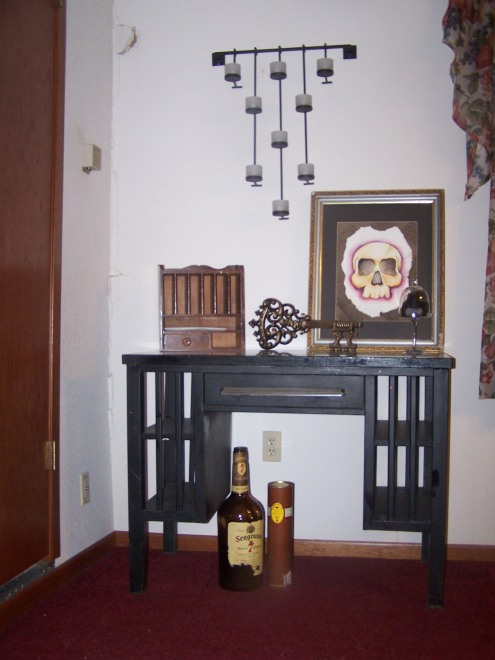 This is a little corner of the dining room. The door leads down to an old basement. This was a hand-me-down metal desk. We fell in love with it. We don't really use it as a desk, but more as a table and storage (the house has NO extra linen-type closets!). The little jar is a bag of HUGs! The paiting is one by my brother, which he gave me for my birthday this year. I love this little area.