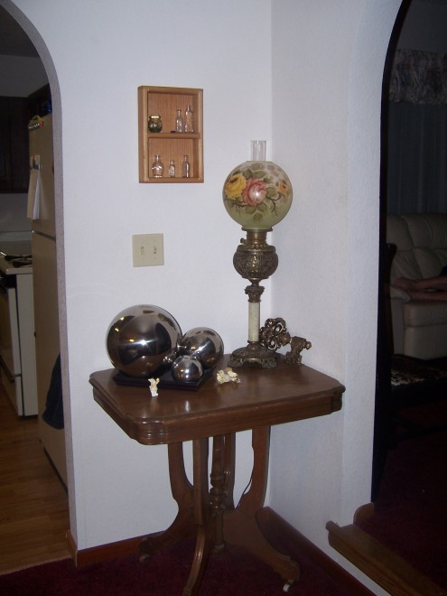 This is the corner of the dining room between the kitchen and the living room.  The antique table and antique lamp are from my grandmother.  The silver balls are modern and I think provide nice contast here.  The little primitive box was one that Tony made when he was in high school.  I think its adorable.  I added antique bottles.