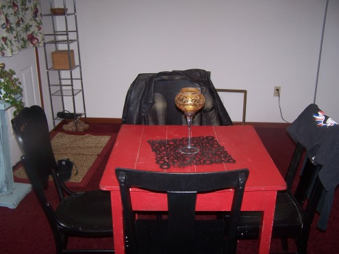 This is our little red dining room table. The mismatched chairs are all painted black. if you can see the curtains here or in any other pictures, they, too, need to be replace. They are covered in fruit. Its on the project list!