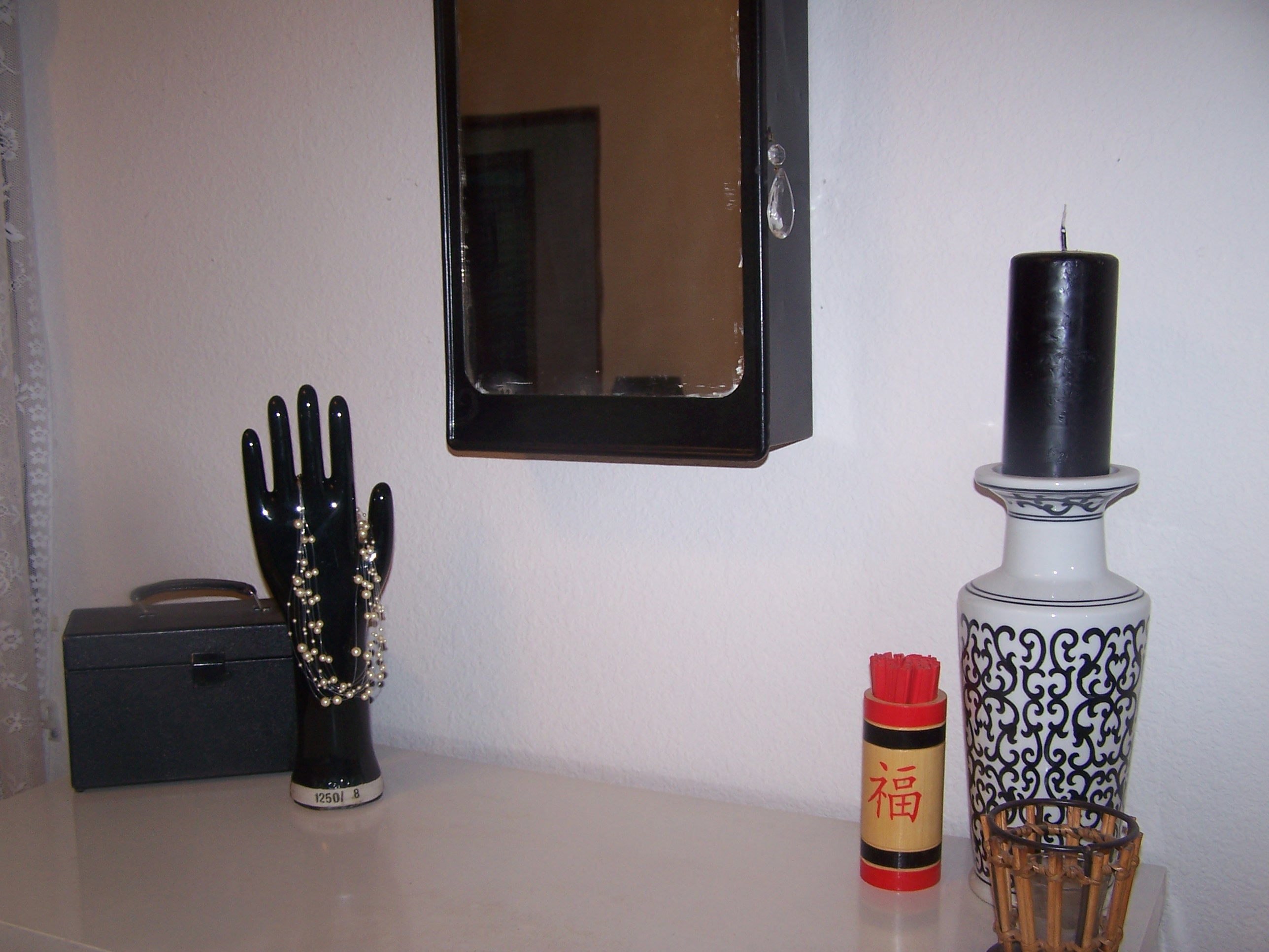 The hand is a vintage glove mold, the box is an old Kodak box, which we keep our momentos in. The mirror is an antique medicine cabinet, which we painted black and added a chendelier crystal for a pull.