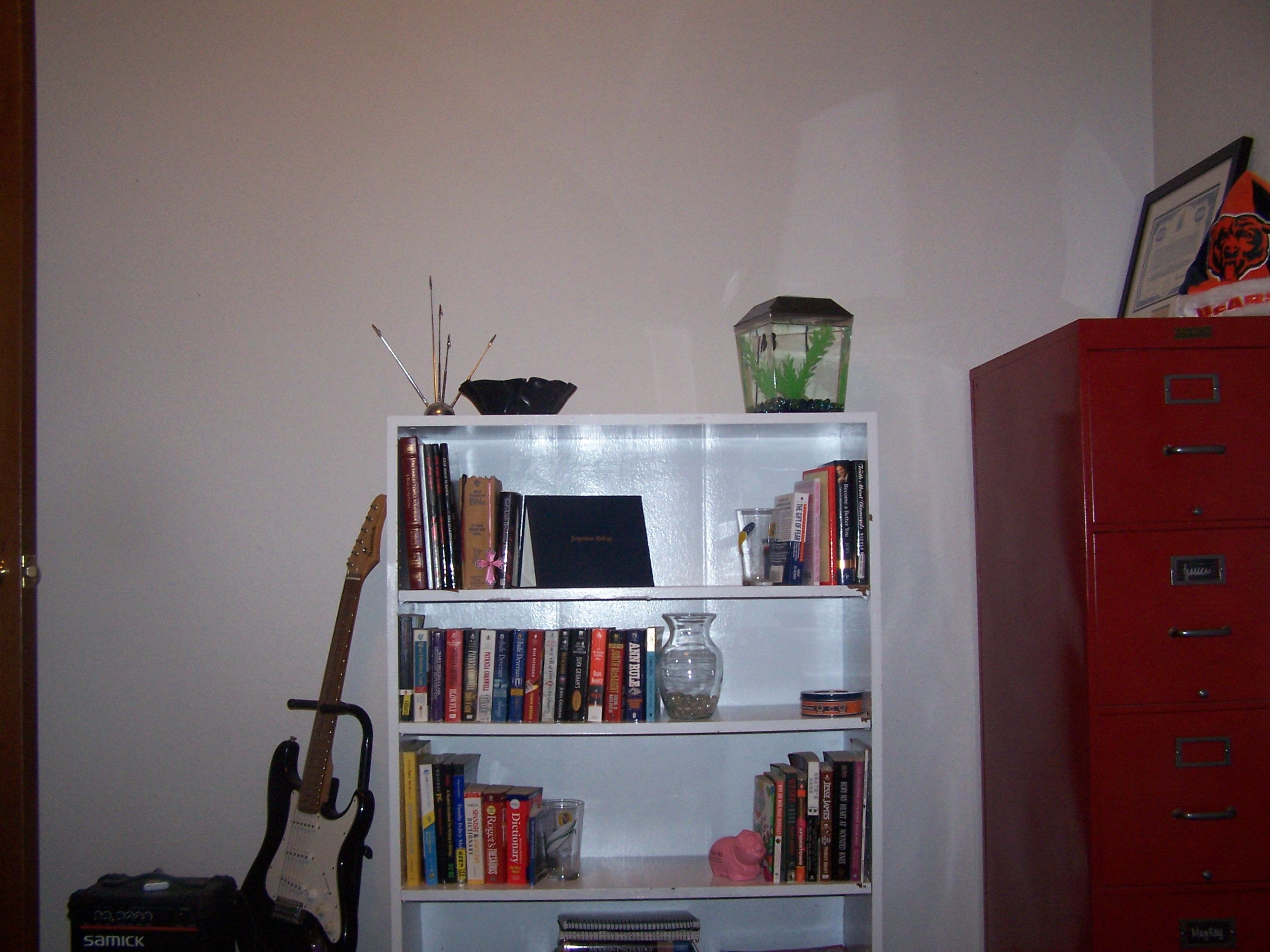 This is the wall that the futon faces. The bookshelf holds all of our school books. Above that is empty because it is for the projection screen. We have a large frame for the area, but it has yet to be hung. The file cabinet is an old Shaw-Walker that I painted bright red.