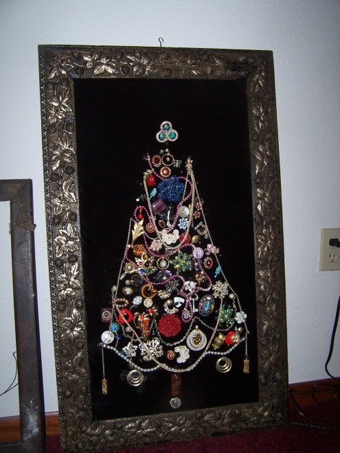 This is a Christmas tree made out of my grandma's antique jewelry.  What a cool idea!  It is framed in a very old frame and there are Christmas lights behind the black velvet.  It is really so cute that I might have to leave it our all year!