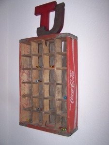 A worn coke crate is hung up in our bedroom.
